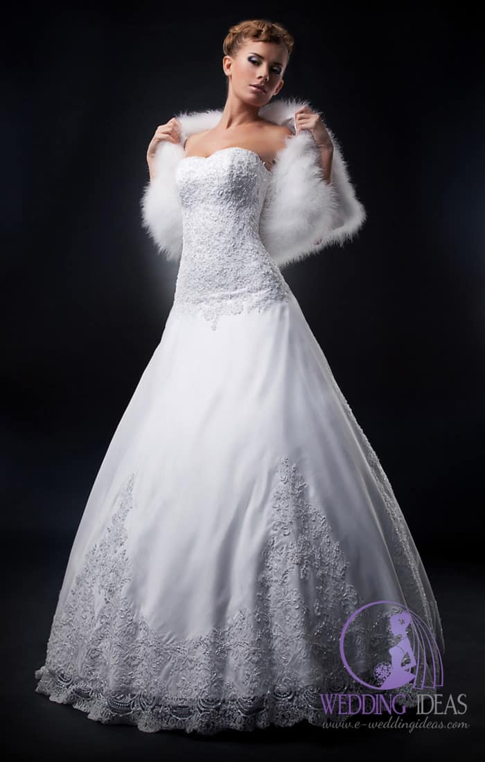 187. Ball gown with sweetheart necklace. Lace design on the bodice, smooth skirt with lace design on the bottom. White fur hold in both hands near her arms.