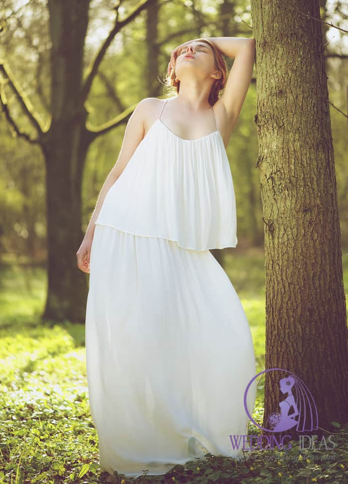 188. Pleated two layer vintage look bride dress on spaghetti strap. Head put on the back, short brown hair and no makeup on the eyes, with matt pink lips. Forest in the background.