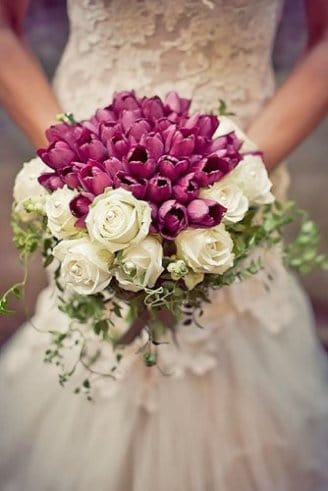 white and purple flowers and strings of green leaves held by the bride in white