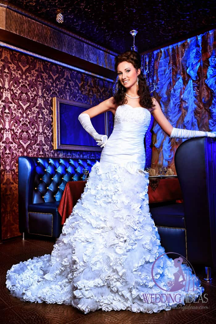 Bottom on the back of dress and long black hair. Very long floral look tulle train. Dark wall like a scenery show better a details of grown.