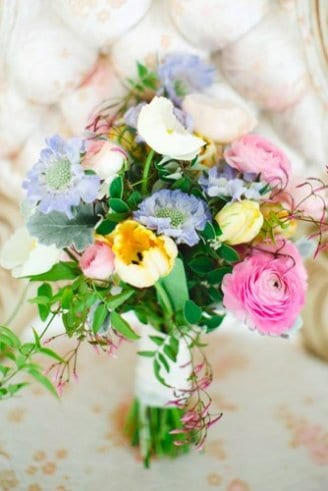 An adorable wedding bouquet consisting of pink, blue, yellow and green flowers tied with a white ribbon