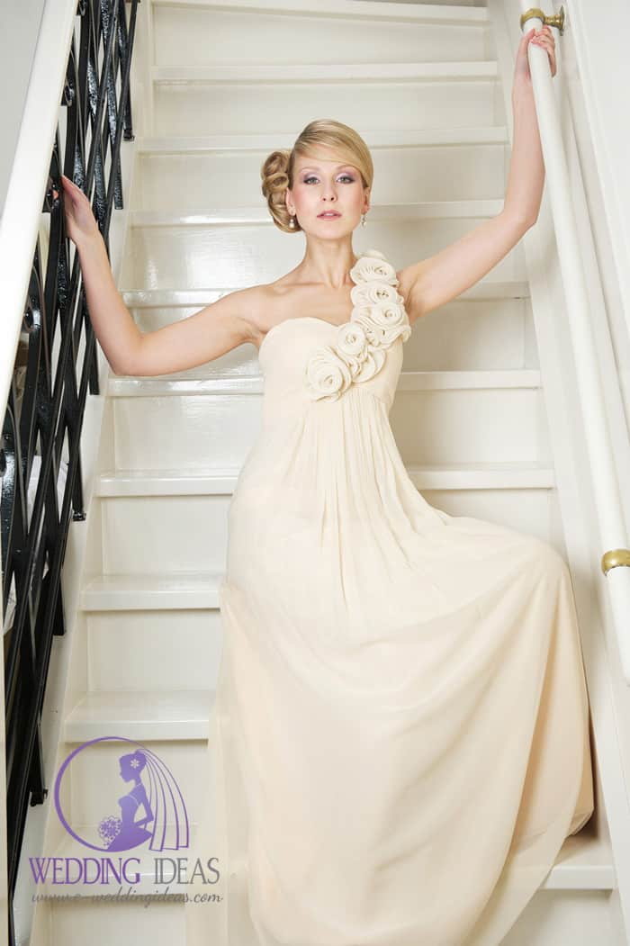 A-line gown with sweetheart necklace and rose material asymmetric strap. Pleated on the waist. Whole bride dress in beige color. Pinned up blond hair and delicate elegant makeup.