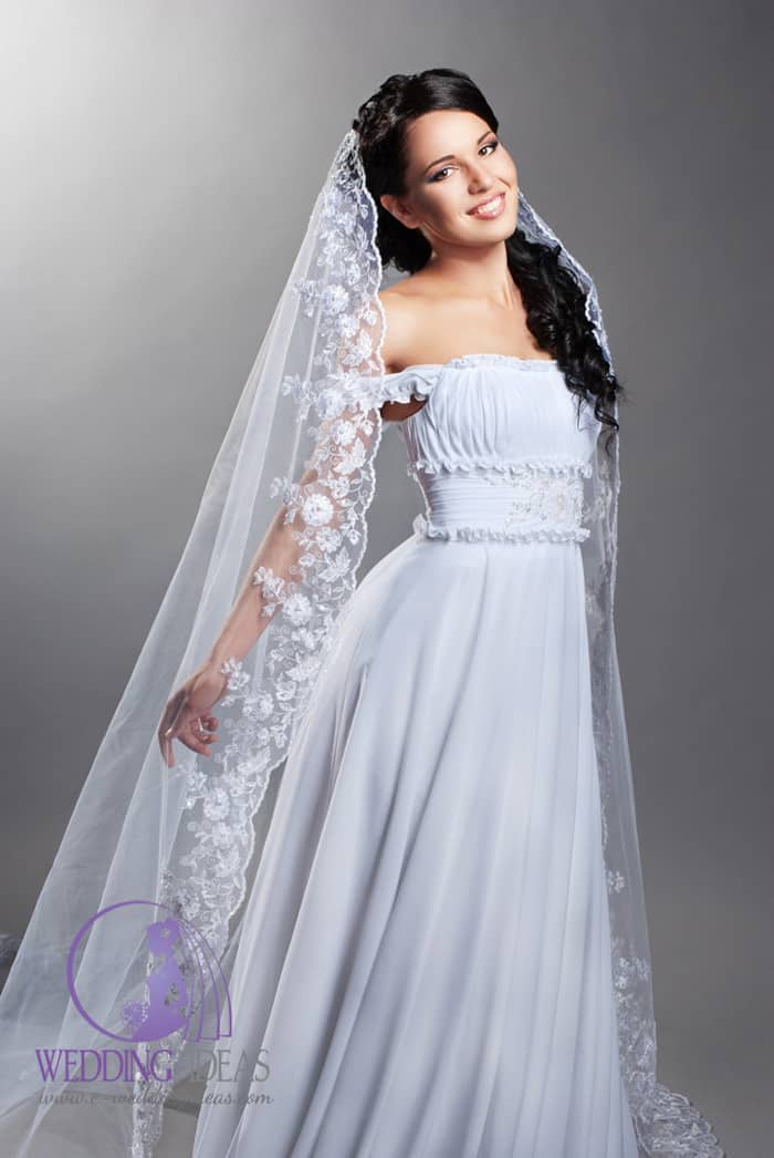 192. Off-shoulder wedding dress pleated on the bust, wide belt with crystal design in the waist. Very long veil with lace flower design on the end pinned in black hair.
