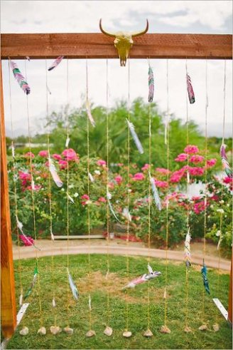 A wooden photo-shooting stand made of hanging strings in front of red roses.