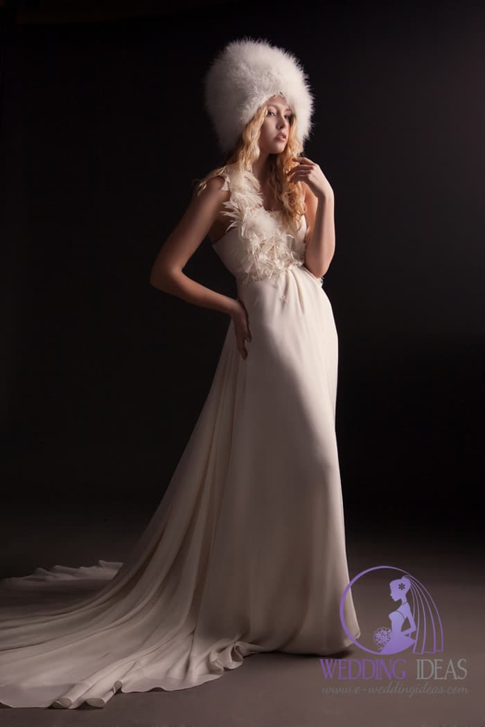 196. A-line satin wedding dress with straight necklace, and one tulle strap on right side. Faux fur hat on the head hide curly blonde hair. Very long train going from smooth skirt.