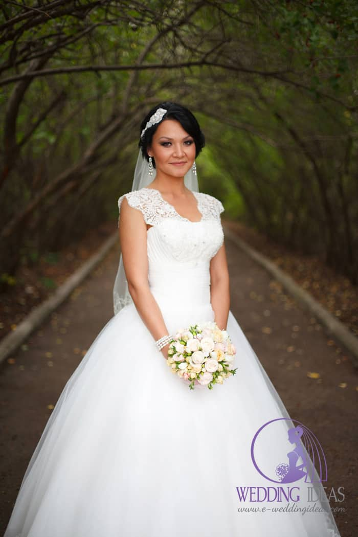 Long elegant lace wedding dress with queen Anne necklace. Pearl jewelry is delicate and elegant as well. Everything is white only a colorful bouquet makes this styling a little bit more interesting.