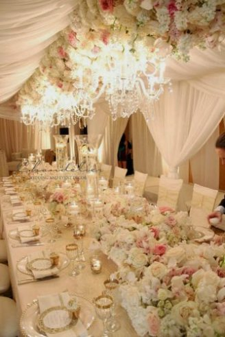 A lovely white wedding tent with white seats, white lighting and hanging green flowers
