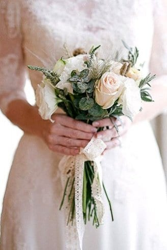 A small but lovely wedding bouquet made of beautiful green leaves and round white flowers tied with a white ribbon