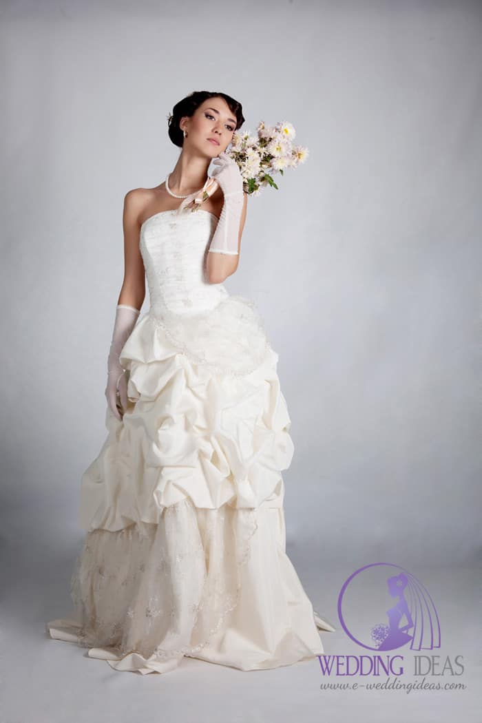 Straight satin necklace and layered skirt in ivory with a bow on the back.