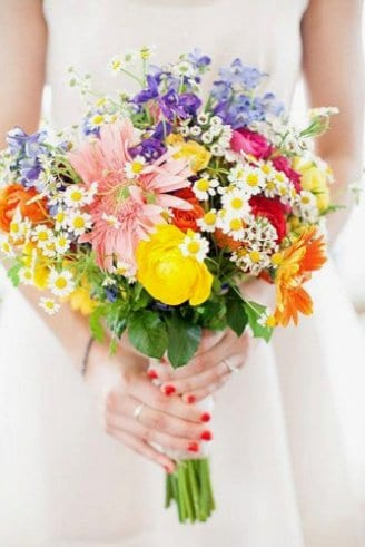 A romantic wedding bouquet comprised of yellow, white, purple, red and green flowers