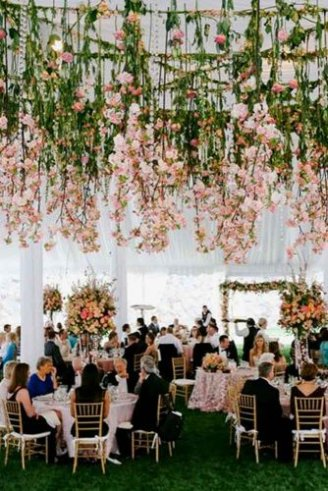 An exquisite white wedding tent with pink seats, pink table clothes and hanging green flowers