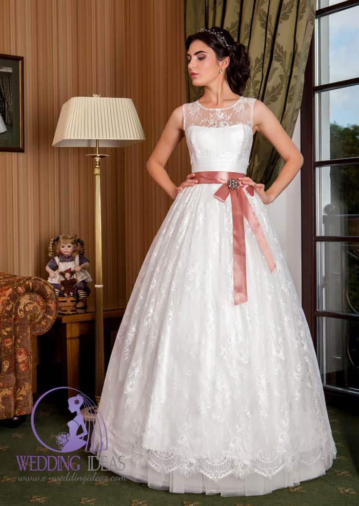 A-line gown with lace illusion necklace. Lace design on the bodice and one lace layer on the tulle skirt. Dusty pink ribbon on the waist with bow