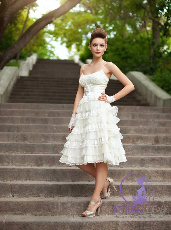 Wedding dress has style spaghetti strap with crystal clip in bodice and short layered skirt