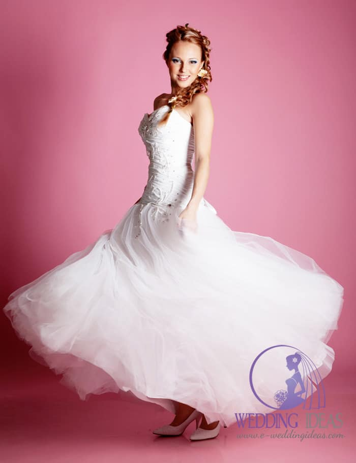 Sweetheart necklace with tulle skirt with bow on the back. Elegant white heels. Flowers in the hair make this hair style different than others.