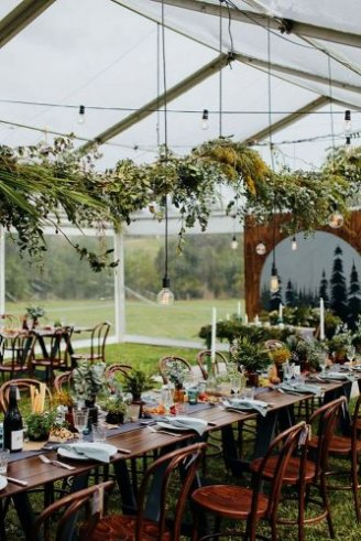 A lovely pink wedding tent with white seats and green flowers