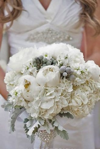A beautiful bouquet consisting of white flowers, mixed with grey leaves and grey fruits held by the bride