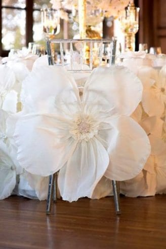 A wedding reception table laid with a white tablecloth wine glasses and white synthetic flowers.