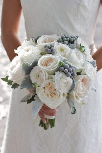 An adorable wedding bouquet made of large white flowers and grey fruits and leaves
