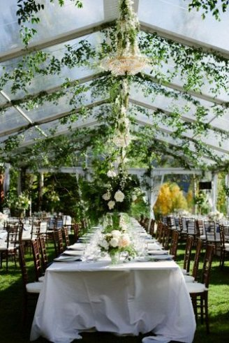 An exquisite white wedding tent with brown seats, white table clothes and green flowers