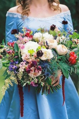 A lovely bouquet consisting of round white and red flowers mixed with green, purple, black and blue leafy flowers