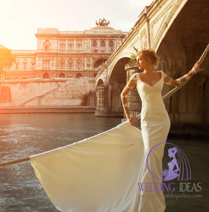 A-line gown with a V-neck, long lace sleeves, and satin skirt with train.