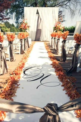 A white carpet with brown flowers on its side leading to a stage made with white sheets of cloth.