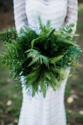 bouquet consisting of green leaves held by the bride in white