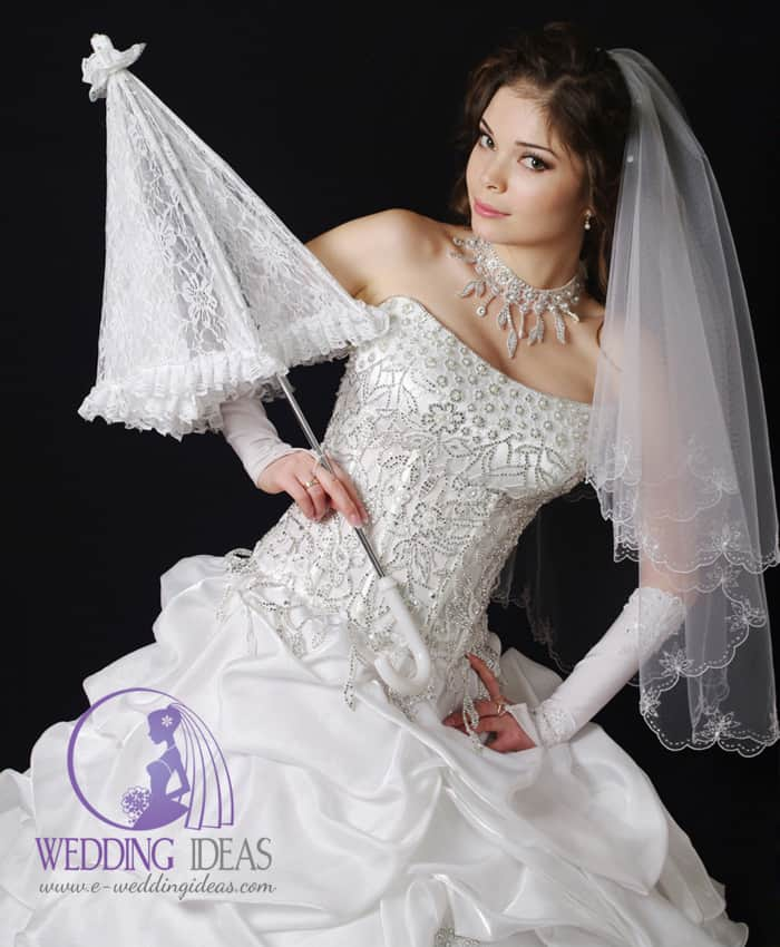 Strapless ball bride dress with straight neck and bodice in pearls and crystals and layered satin skirt.