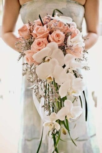 bouquet comprised of round pink and white flowers and green and purple flowers