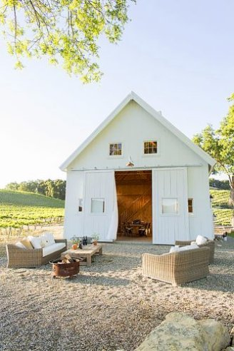 Three sofas set outside an entrance to a white wooden hall.
