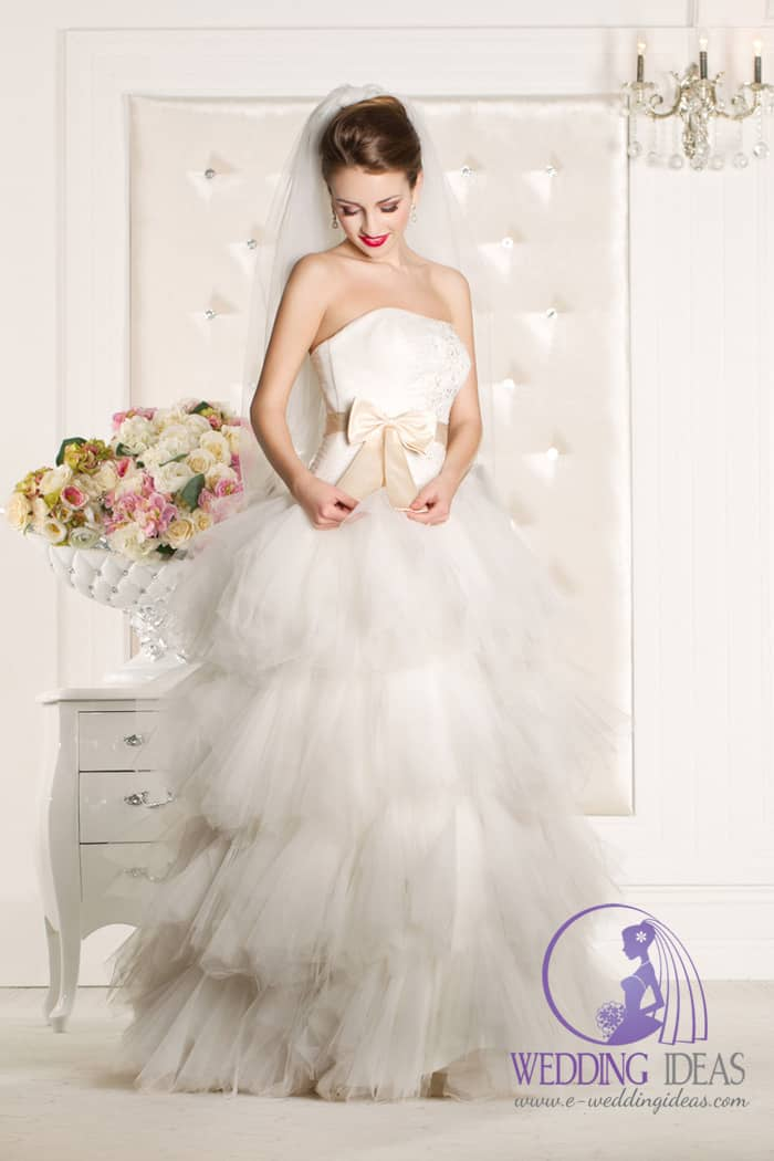 Strapless ball wedding dress with a straight neckline and beige bow in the waist and tulle layered skirt