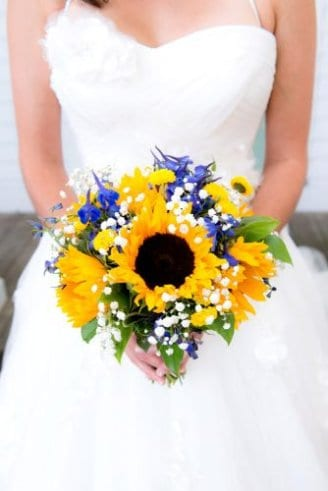 bouquetof white and blue flowers, sunflowers and green leaves