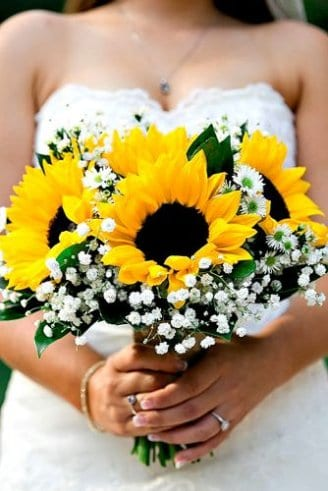 A lovely wedding bouquet consisting of small white flowers, green leaves and sunflowers