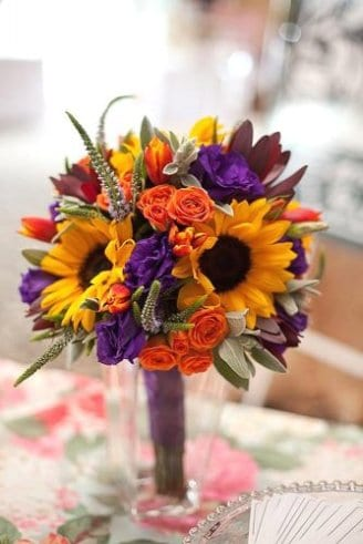 A wonderful bouquet consisting of purple and orange flowers mixed with sunflowers and green leaves held by the bride
