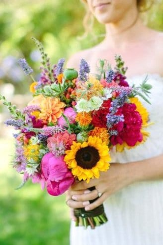 A beautiful multi-colored bouquet comprised of large purple, green, blue and orange flowers including several sunflowers