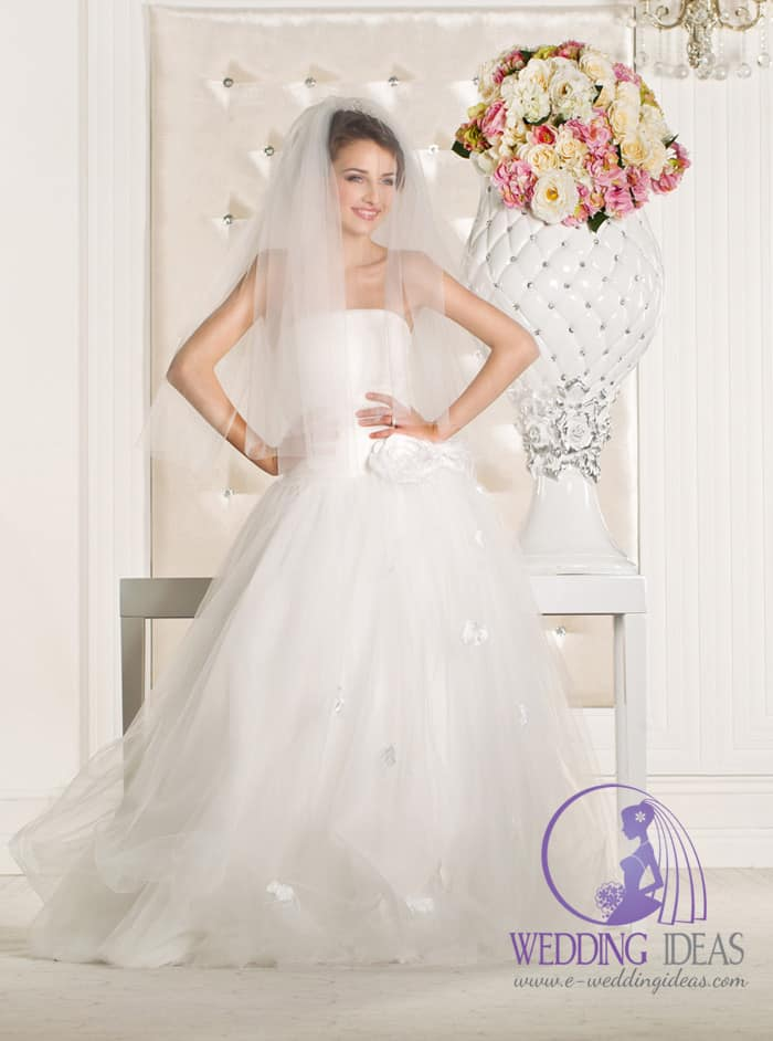 Strapless ball bride dress with straight necklace and white rose at the end of the bodice.