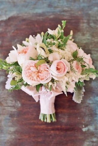 large round pink and green leafy flowers and green flower buds held by the bride