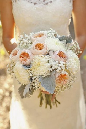 A beautiful bridal bouquet consisting of small white flowers, big pink flowers and grey leaves