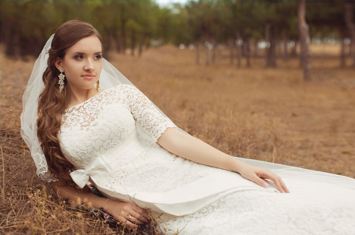 bride laying in a brown field