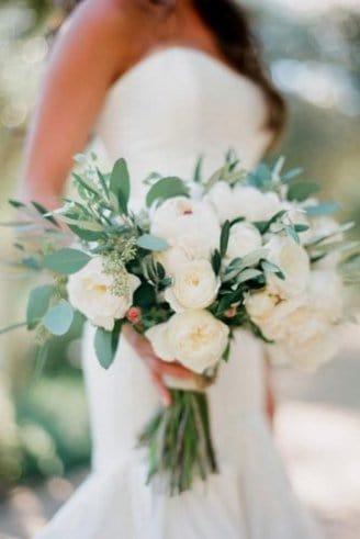 A stunning bouquet consisting of round white flowers mixed with green leaves held by the bride