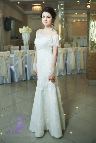 A unique white dress with a straight bust and short, flowery sleeves