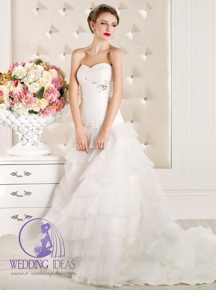 40. Sweetheart necklace with crystal flowers in the bodice and layered tulle skirt with train. Crystal diadem in the hair and pearl earrings. Light makeup and pink lips.
