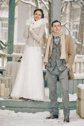 A groom in a light brown trench court, grey sleeveless blazer, white shirt, grey and white tie a light brown scarf and black shoes