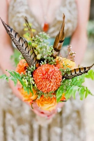 A small but charming bouquet made of one round orange-colored flower, green leaves and black and brown feathers