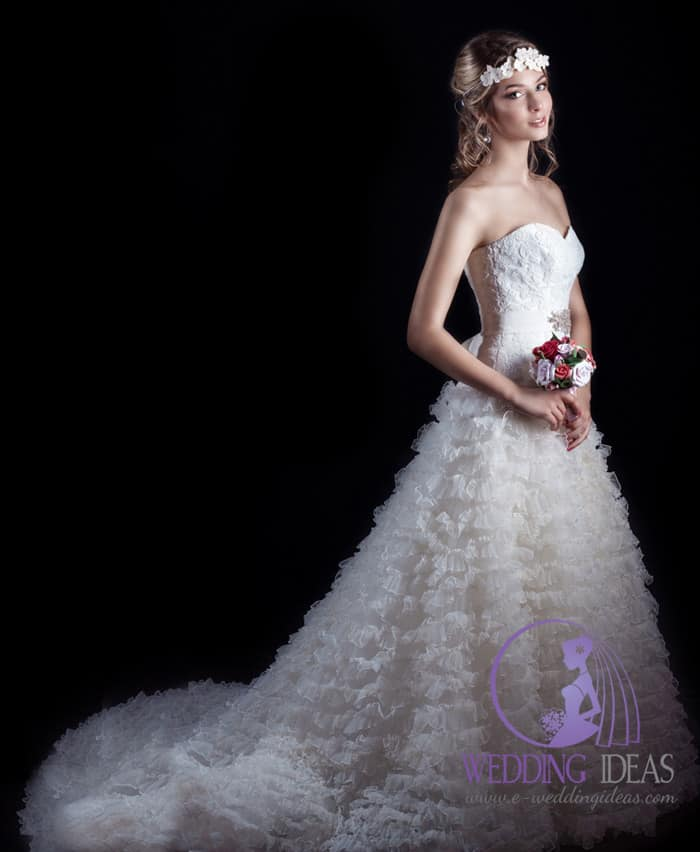 Strapless sweetheart neckline with a lace bodice and layered tulle skirt with train, satin belt with crystals on the waist.