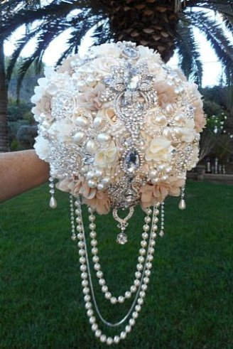 A synthetic bouquet made of white flowers and strings of shiny balls and other shining beads all over it