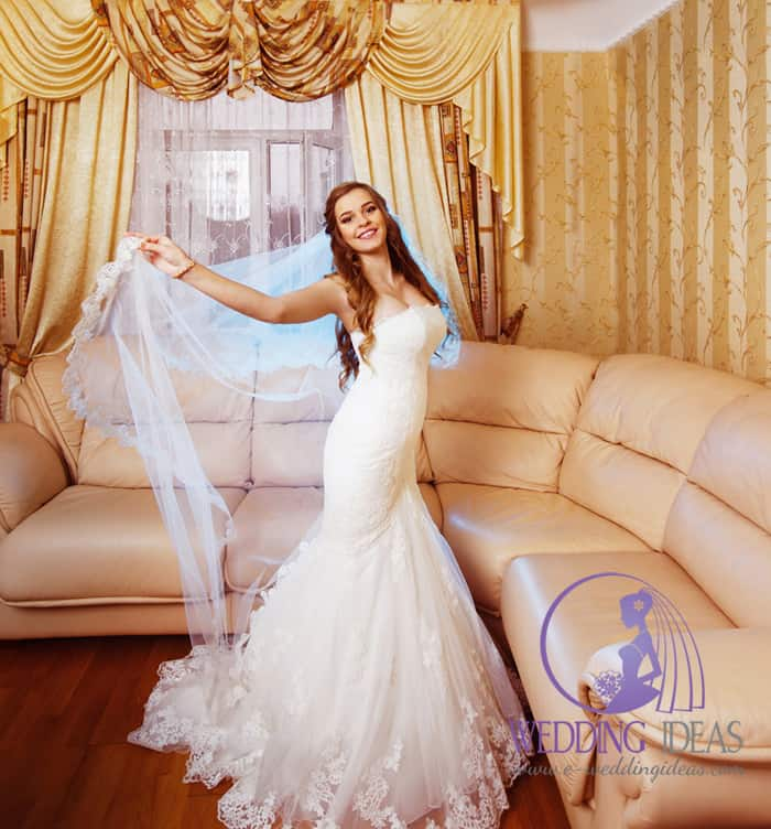 Lace straight neckline and tulle mermaid skirt with lace elements. Long veil with lace on the end.