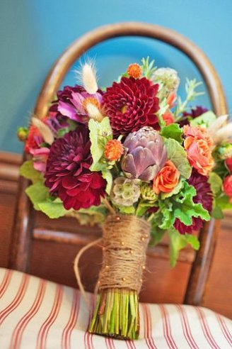 A cool bouquet made of purple, blue and white flowers and green leaves