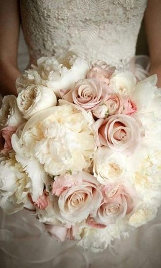 A beautiful bouquet consisting of white and pink flowers, mixed with green flower buds held by the bride