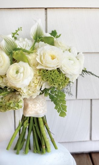 A lovely wedding bouquet made of round white and green leafy flowers